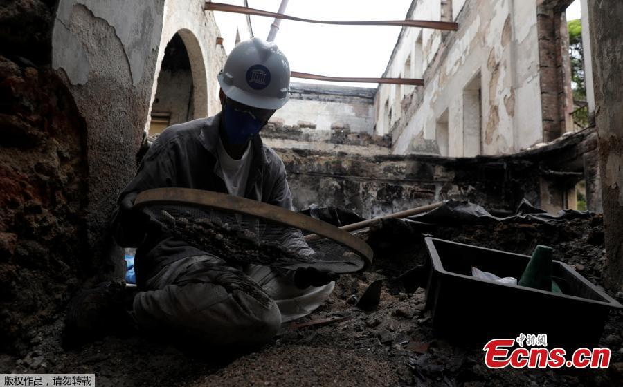 A staffer of Brazil National Museum works on searching and saving artefacts after its devastating fire, in Rio de Janeiro, Brazil, Feb. 12, 2019. Five months after fire gutted Brazil\'s 200-year-old National Museum, the site that once held some of the nation\'s greatest treasures remains a ruin of scorched walls, twisted metal and piles of ash. (Photo/Agencies)