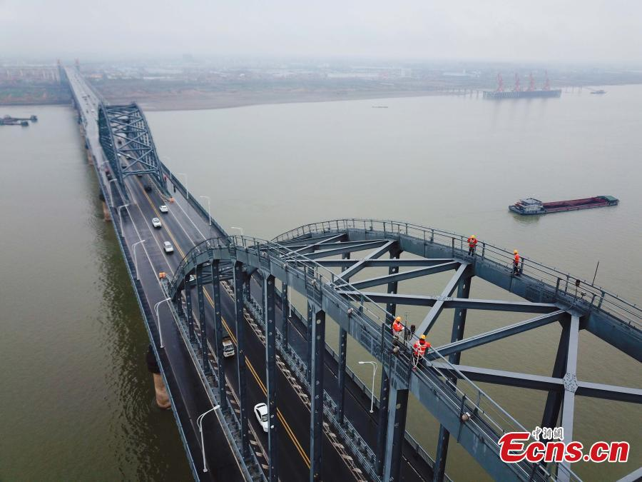 Technicians conduct a routine safety check on the Jiujiang Yangtze River Bridge, a major connection of the Beijing-Kowloon Railway in Jiujiang City, East China\'s Jiangxi Province during the travel peak of the Spring Festival. Despite the wind and vibration caused by the passing trains, they continued working in baskets hung under the bridge\'s girder, about 20 meters above the rolling Yangtze River. (Photo: China News Service/Ding Bo)