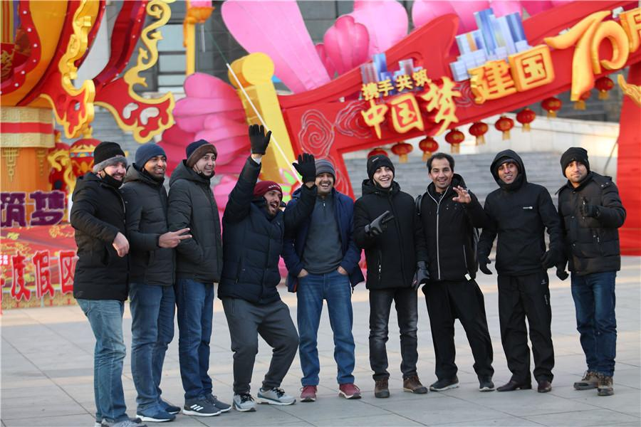 International friends pose for a group photo in front of the main lantern of the Lantern Festival in Dalian, Northeast China\'s Liaoning province, on Feb 7, 2019. (Photo by Ma Chengjun/For chinadaily.com.cn)