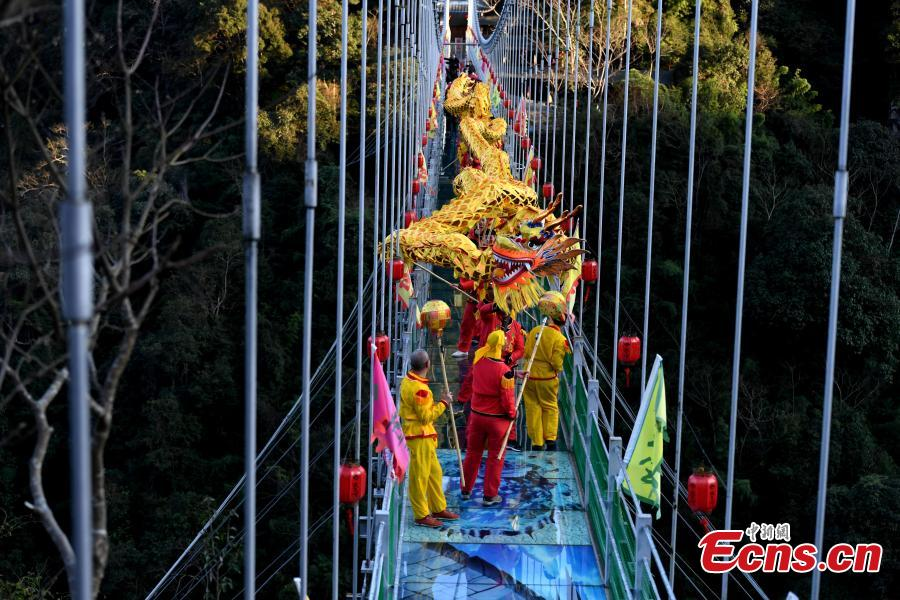 As part of Spring Festival celebrations, local people perform a dragon dance on a suspended glass bridge, some 200 meters above the ground, at a scenic area in Youxi County, East China\'s Fujian Province, Feb. 12, 2019.  (Photo: China News Service/Wang Dongming)