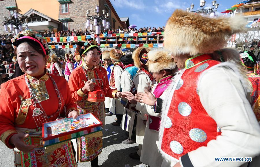 People of Tibetan ethnic group serve alcoholic drink during the Shangjiu Festival at the foot of Jiajin Mountain in the Tibetan Township of Qiaoqi in Ya\'an City, southwest China\'s Sichuan Province, Feb. 13, 2019. The Shangjiu Festival, a traditional festival of the Tibetan people, is celebrated on the ninth day of the first lunar month to pray for a good harvest. (Xinhua/Jiang Hongjing)