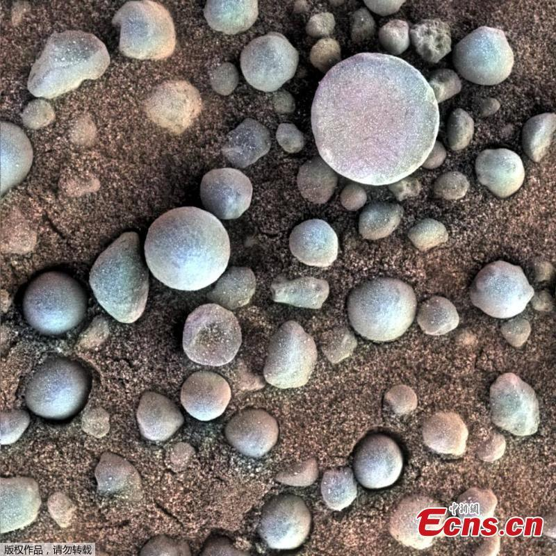 These tiny spherules pepper the sandy surface in this 3-centimeter square view of the Martian surface. Opportunity took this image while the target was shadowed by the rover\'s instrument arm. (Photo/VCG)