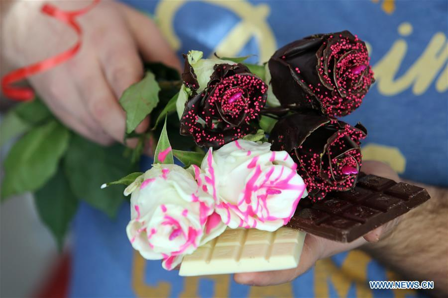 Photo taken on Feb. 13 shows chocolate-coated roses held by Ante Jurkovic, owner of a flower shop in Rijeka, Croatia, Feb. 13, 2019. Jurkovic invented the technic to coat roses with chocolate in preparation for Valentine\'s Day. (Xinhua/Goran Kovacic)
