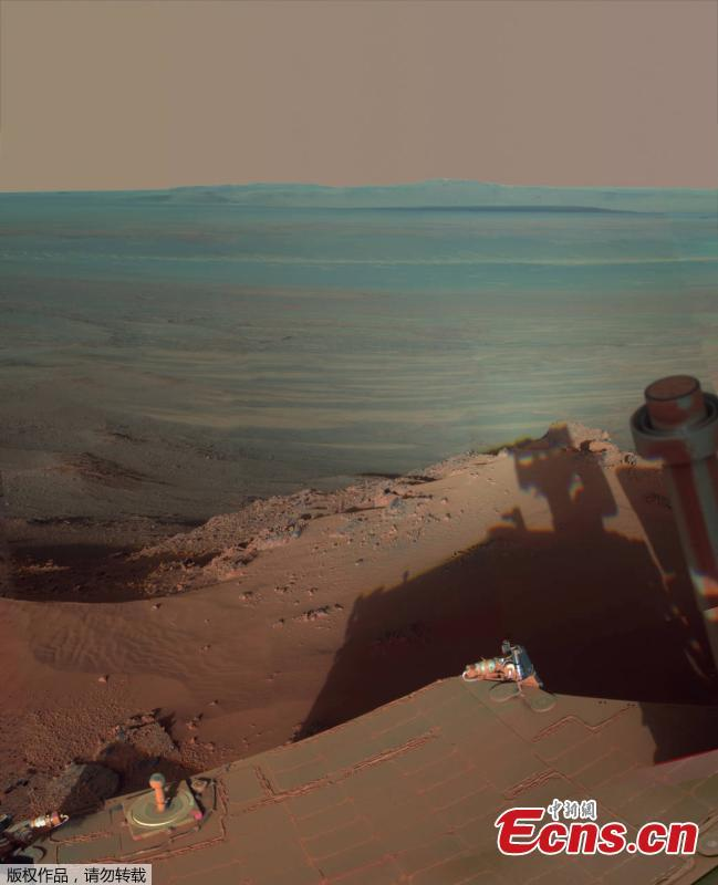 Opportunity catches its own late-afternoon shadow in this dramatically lit view eastward across Endeavour Crater on Mars, May 22, 2012. he scene is presented in false color to emphasize differences in materials such as dark dunes on the crater floor. (Photo/VCG)
