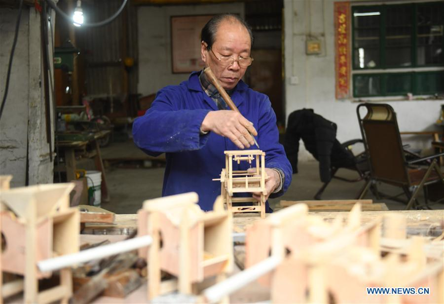 Lin Shunkui shows his tools for making ornamental dragon at home in Beibaixiang Town of Yueqing, east China\'s Zhejiang Province, Feb. 11, 2019. Having a history of more than 400 years, the ornamental dragon, a sacrifice to pray for good fortune during the period of Lantern Festival, is popular in villages of Yueqing City in Zhejiang Province. Lin Shunkui, an inheritor of the handicraft of ornamental dragon, is born in 1956 in Dongchan Village of Beibaixiang Town. Learning the art since he was young from his father, who is a master of fine paper-cutting, Lin has been in the walk for more than 40 years and has been famous for his exquisite handicraft. The making procedures of the ornamental dragon require high standards and needs preparation of more than half a year. The craftsman must be proficient in various vocations such as paper-cutting, carpentry, painting and machinery. Usually having a height of four meters, a length of three meters and a width of two meters, the ornamental dragon displays about 300 figures in more than 80 cabinets, which are driven by gears hidden inside the dragon body. The handicraft of ornamental dragon was listed as one of the national intangible cultural heritages in October of 2014. (Xinhua/Weng Xinyang)