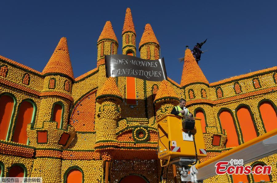 A worker puts the final touch to a sculpture made with lemons and oranges which depicts a Castle during the 86th Lemon festival around the theme \