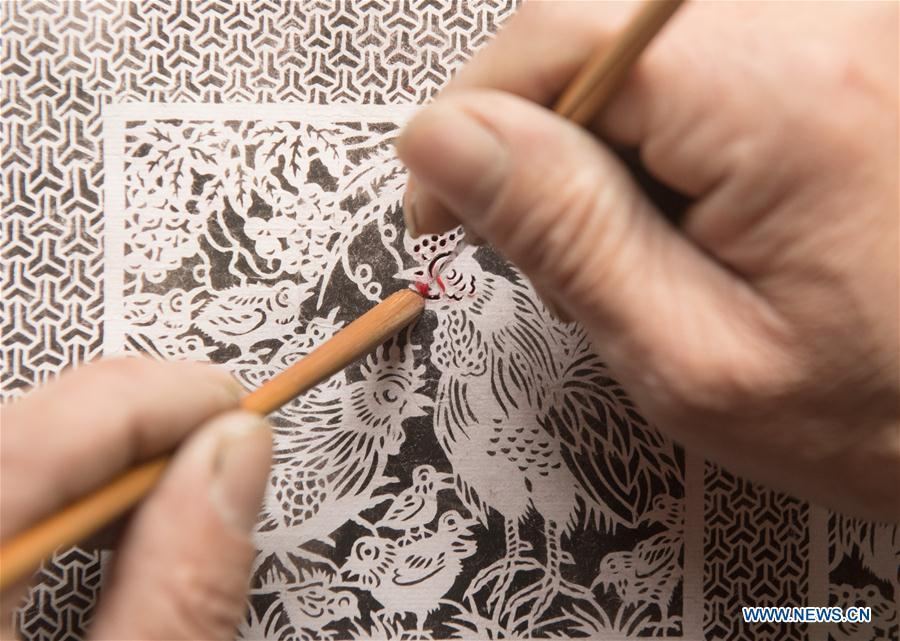 Lin Shunkui shows paper-cutting skills at home in Beibaixiang Town of Yueqing, east China\'s Zhejiang Province, Feb. 12, 2019. Having a history of more than 400 years, the ornamental dragon, a sacrifice to pray for good fortune during the period of Lantern Festival, is popular in villages of Yueqing City in Zhejiang Province. Lin Shunkui, an inheritor of the handicraft of ornamental dragon, is born in 1956 in Dongchan Village of Beibaixiang Town. Learning the art since he was young from his father, who is a master of fine paper-cutting, Lin has been in the walk for more than 40 years and has been famous for his exquisite handicraft. The making procedures of the ornamental dragon require high standards and needs preparation of more than half a year. The craftsman must be proficient in various vocations such as paper-cutting, carpentry, painting and machinery. Usually having a height of four meters, a length of three meters and a width of two meters, the ornamental dragon displays about 300 figures in more than 80 cabinets, which are driven by gears hidden inside the dragon body. The handicraft of ornamental dragon was listed as one of the national intangible cultural heritages in October of 2014. (Xinhua/Weng Xinyang)