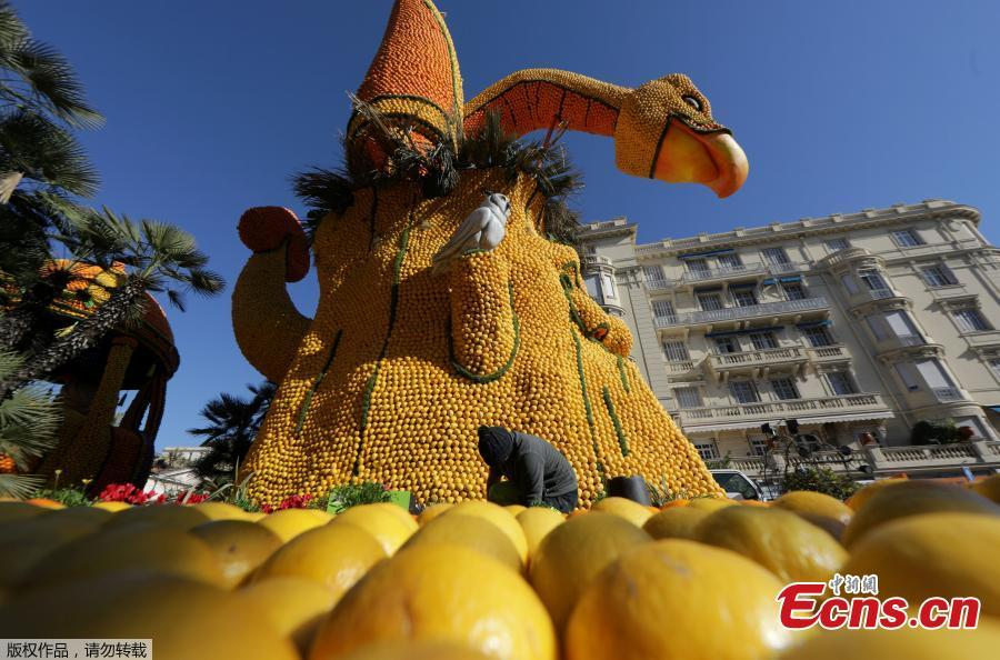 A worker puts the final touch to a sculpture made with lemons and oranges which depicts Dragon Nest during the 86th Lemon festival around the theme \