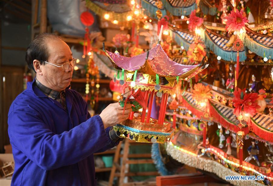 Lin Shunkui looks at his ornamental dragon at home in Beibaixiang Town of Yueqing, east China\'s Zhejiang Province, Feb. 11, 2019. Having a history of more than 400 years, the ornamental dragon, a sacrifice to pray for good fortune during the period of Lantern Festival, is popular in villages of Yueqing City in Zhejiang Province. Lin Shunkui, an inheritor of the handicraft of ornamental dragon, is born in 1956 in Dongchan Village of Beibaixiang Town. Learning the art since he was young from his father, who is a master of fine paper-cutting, Lin has been in the walk for more than 40 years and has been famous for his exquisite handicraft. The making procedures of the ornamental dragon require high standards and needs preparation of more than half a year. The craftsman must be proficient in various vocations such as paper-cutting, carpentry, painting and machinery. Usually having a height of four meters, a length of three meters and a width of two meters, the ornamental dragon displays about 300 figures in more than 80 cabinets, which are driven by gears hidden inside the dragon body. The handicraft of ornamental dragon was listed as one of the national intangible cultural heritages in October of 2014. (Xinhua/Weng Xinyang)