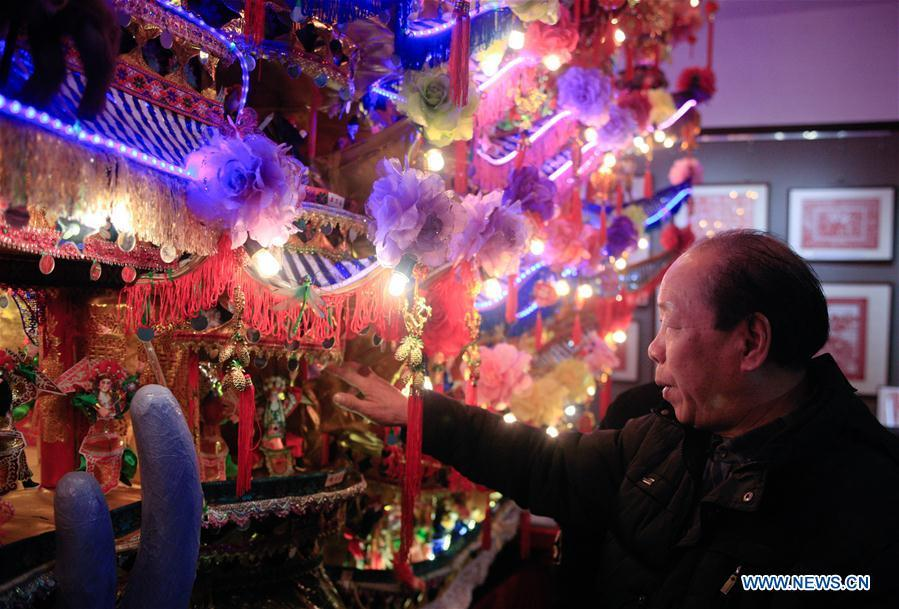 Lin Shunkui looks at his ornamental dragon at home in Beibaixiang Town of Yueqing, east China\'s Zhejiang Province, Feb. 11, 2019. Having a history of more than 400 years, the ornamental dragon, a sacrifice to pray for good fortune during the period of Lantern Festival, is popular in villages of Yueqing City in Zhejiang Province. Lin Shunkui, an inheritor of the handicraft of ornamental dragon, is born in 1956 in Dongchan Village of Beibaixiang Town. Learning the art since he was young from his father, who is a master of fine paper-cutting, Lin has been in the walk for more than 40 years and has been famous for his exquisite handicraft. The making procedures of the ornamental dragon require high standards and needs preparation of more than half a year. The craftsman must be proficient in various vocations such as paper-cutting, carpentry, painting and machinery. Usually having a height of four meters, a length of three meters and a width of two meters, the ornamental dragon displays about 300 figures in more than 80 cabinets, which are driven by gears hidden inside the dragon body. The handicraft of ornamental dragon was listed as one of the national intangible cultural heritages in October of 2014. (Xinhua/Zhu Weixi)