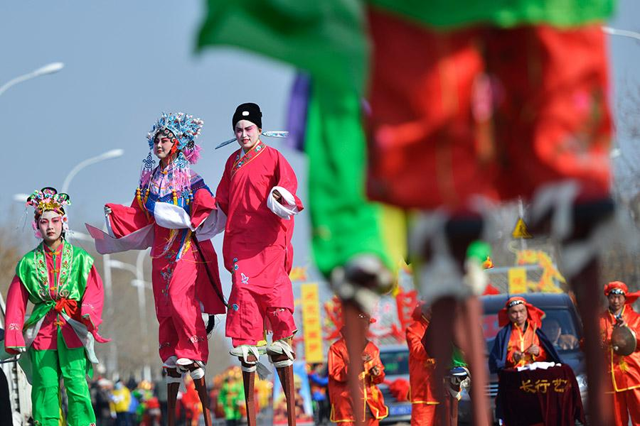 Local performers walk on stilts to celebrate the festival in Zibo, Shandong Province, in March 2018. (PHOTO BY DONG NAIDE/FOR CHINA DAILY) These days, though, ice lanterns have become larger in size and are often combined with elaborately engraved designs, and the candle has gradually been replaced by a light bulb and, in some cases, even laser lights. The shapes range from small animals, like rabbits, to representations of large structures, such as city walls. The ice engraved lanterns are becoming a folk art all of their own.  Solving lantern riddles is another Lantern Festival tradition. The riddles are written one by one on separate slips of red paper and pasted under the lanterns-the right answer will win a gift for the bright mind who solves the puzzle.  Folk art activities with auspicious meanings, such as lion and dragon dancing, are also part of the celebration of the first full moon of the lunar year. Traditionally, the celebration of Lantern Festival also marks the end of the Spring Festival holiday.