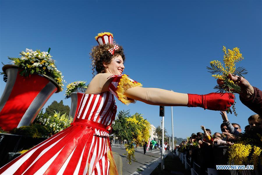 A performer distributes flowers during the parade of Nice Carnival with the theme \