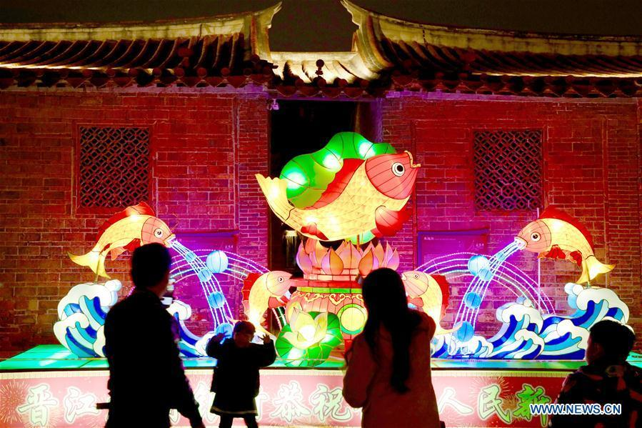 A young visitor poses for photos with a festive lantern at the Wudianshi historical community in Jinjiang, southeast China\'s Fujian Province, Feb. 17, 2019. More than 3,000 festive lanterns have been set in three dedicated zones in Jinjiang ahead of the Lantern Festival, which falls on Feb. 19 this year and marks the end of the Chinese Lunar New Year celebrations. (Xinhua/Jiang Kehong)
