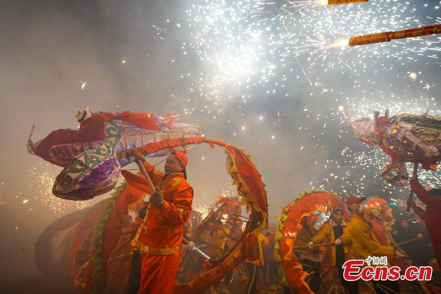 People perform dragon dance with a background of firecrackers in Yuqing County, southwest China\'s Guizhou Province, Feb. 16, 2019. Villagers gathered and performed dragon dances to celebrate the upcoming Lantern Festival,which falls on Feb. 19 this year. (Photo/China News Service)