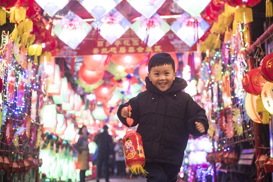 A boy runs happily in a corridor lit up with lanterns to celebrate Lantern Festival in Baibuting community, Wuhan, Hubei Province, in March 2018. (PHOTO/XINHUA)  As the first full moon of the new year approaches, China prepares to celebrate Lantern Festival.  Lantern Festival, or yuanxiaojie in pinyin, which comes on the 15th day of the first lunar month, is the first festival after the celebration of Lunar New Year in China.  The tradition dates back to more than 2000 years ago-during the Han Dynasty (206 BC-AD 220) when Buddhism was flourishing in China. Emperor Ming of the Eastern Han Dynasty (25-220) ordered that lanterns be lit in the imperial palace to worship and show respect for Buddha.  During the reign of Emperor Yang of the Sui Dynasty (581-618), a large-scale gala with thousands of people was held over the course of the night to celebrate Lantern Festival.  The tradition of lighting lanterns gradually became a civilian activity, and the lanterns are now made into different sizes, shapes and colors-but all have good wishes for the new year.