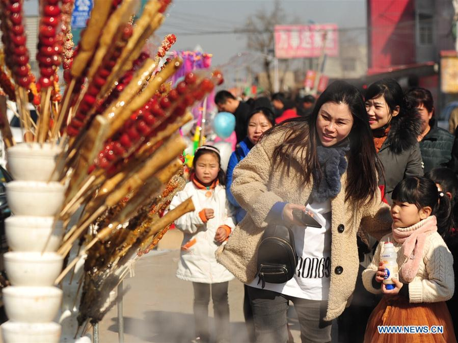 Tourists walk past booths selling tanghulu, a traditional Chinese snack of candied fruit, during an activity to greet the upcoming Lantern Festival in Lihua Village of Renqiu, north China\'s Hebei Province, Feb. 17, 2019. The traditional Chinese Lantern Festival falls on Feb. 19 this year. (Xinhua/Mu Yu)