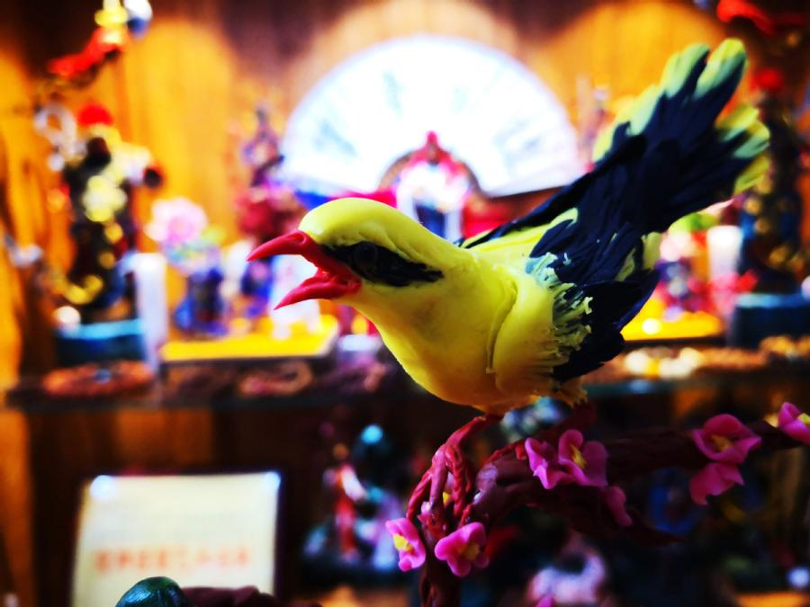 This almost lifelike dough figurine of a bird is created by Gong Yuze. (Photo by Zhang Qingyun for chinadaily.com.cn)
