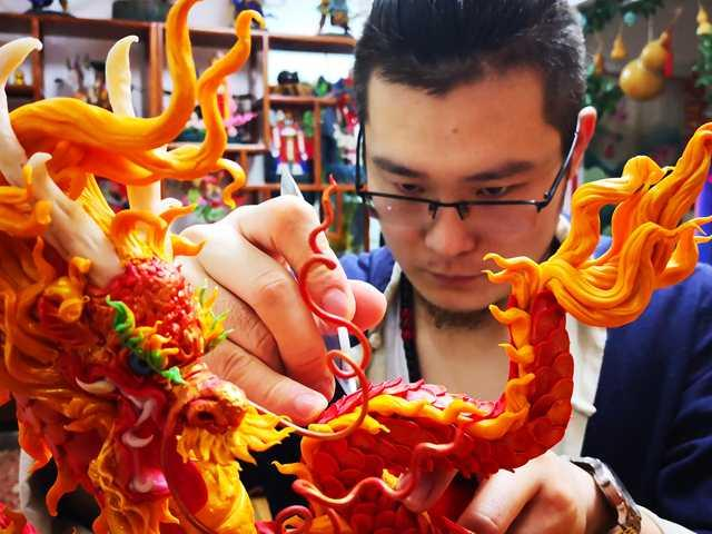 Gong Yuze concentrates intensively as he works on a dough figurine in his studio in Harbin, capital of Northeast China\'s Heilongjiang Province.  (Photo by Zhang Qingyun for chinadaily.com.cn)