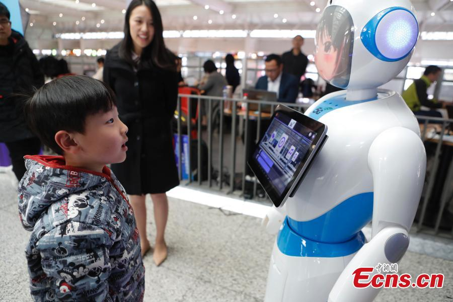 """A boy interacts with a robot at a 5G experience zone at the Hongqiao Railway Station in Shanghai, Feb. 18, 2019. China Mobile has plans to turn the station into the first of its kind in China to offer extensive 5G use options for passengers. (Photo: China News Service/Yin Liqin)  The world\'s first """"5G railway station"""" will debut in Shanghai this year, delivering easy access to super-fast 5G network services for all passengers."""