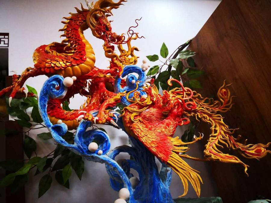 A dough figurine that includes a dragon is created in vivid colors by Gong Yuze. (Photo by Zhang Qingyun for chinadaily.com.cn)