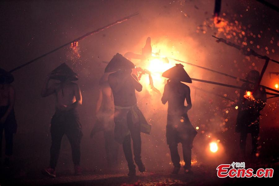 Shirtless men carrying the statue of a local deity perform amid firecrackers and sparklers during a folk festival in Yanfeng Village in Quanzhou City, East China\'s Fujian Province, Feb. 18, 2019. The tradition formed in the Ming Dynasty (1368-1644) is part of Lantern Festival celebrations on the 15th day of the first lunar month, or Feb. 19 this year. (Photo: China News Service/Wang Dongming)