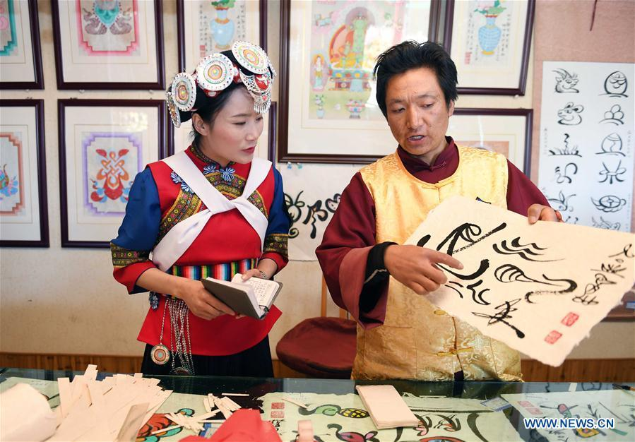 Fan Yongzhen (L), deputy to China\'s 13th National People\'s Congress (NPC), carries out a research on the Dongba pictographic language at Yushuizhai Village of Yulong Naxi Autonomous County in Lijiang, southwest China\'s Yunnan Province, Feb. 13, 2019. Working as vice curator of the Cultural Center in Lijiang city, Fan has devoted herself to the career of protecting and promoting local ethnic cultures. Besides, she also contributes to the mass culture construction work by sending performances to rural areas together with her colleagues. As a deputy to NPC, China\'s top legislature, Fan will put more efforts into the building of cultural industries integrated with digital technologies in underdeveloped areas so as to improve local cultural development. (Xinhua/Yang Zongyou)