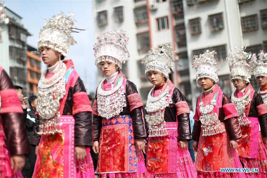 People of the Miao ethnic group dance to the Lusheng, a reed-pipe wind instrument, to celebrate their new life at the relocated Fengle community in Rongjiang County, southwest China\'s Guizhou Province, Feb. 21, 2019. The relocated ethnic Miao people from remote areas to the community held a gathering Thursday by inviting neighboring Miao villages\' Lusheng teams to celebrate their new life.(Xinhua/Yang Chengli)