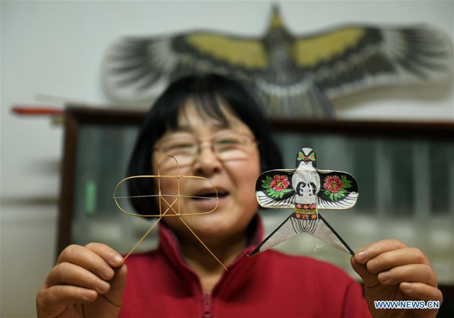 Kite enthusiast Lin Wenqing shows a miniature kite (R) and kite skeleton at home in Shijiazhuang, north China\'s Hebei Province, Feb. 20, 2019. Fu Xianming and his wife Lin Wenqing are known for their passion for kites. The retired school-teacher couple has completed more than 1,500 kites since they began to learn kite-making in 1998. Driven by a wish to master the kite-making crafts, Fu and Lin went on multiple study tours to Weifang, Shandong Province, where traditional Chinese kites originated. Besides enjoying themselves, the couple has also set up a campus workshop for local students who show interest in kite-making. (Xinhua/Chen Qibao)