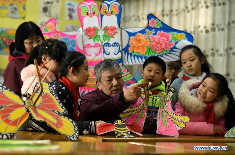 Kite enthusiast Fu Xianming gives a lesson on kite-making during a workshop at Xili Primary School in Shijiazhuang, north China\'s Hebei Province, Feb. 20, 2019. Fu Xianming and his wife Lin Wenqing are known for their passion for kites. The retired school-teacher couple has completed more than 1,500 kites since they began to learn kite-making in 1998. Driven by a wish to master the kite-making crafts, Fu and Lin went on multiple study tours to Weifang, Shandong Province, where traditional Chinese kites originated. Besides enjoying themselves, the couple has also set up a campus workshop for local students who show interest in kite-making. (Xinhua/Chen Qibao)