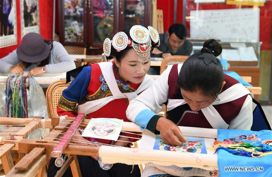 Fan Yongzhen(L, front), deputy to China\'s 13th National People\'s Congress (NPC), carries out a research on dianxiu embroidery at Baisha Old Town of Yulong Nax Autonomous County in Lijiang, southwest China\'s Yunnan Province, Feb. 13, 2019. Working as vice curator of the Cultural Center in Lijiang city, Fan has devoted herself to the career of protecting and promoting local ethnic cultures. Besides, she also contributes to the mass culture construction work by sending performances to rural areas together with her colleagues. As a deputy to NPC, China\'s top legislature, Fan will put more efforts into the building of cultural industries integrated with digital technologies in underdeveloped areas so as to improve local cultural development. (Xinhua/Yang Zongyou)