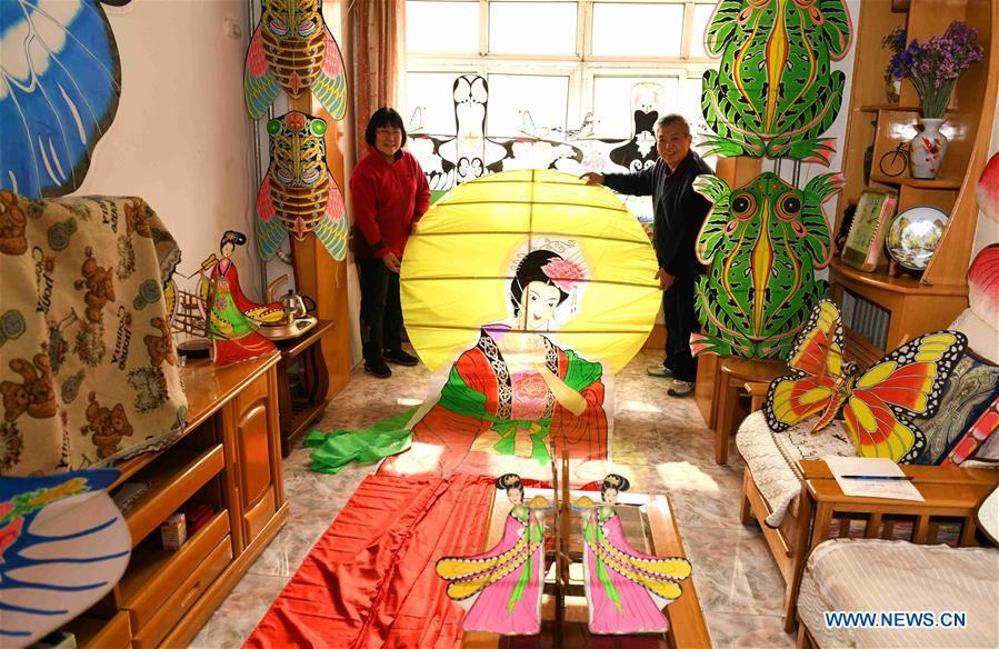 Kite enthusiasts Fu Xianming (R) and Lin Wenqing display one of their kites at home in Shijiazhuang, north China\'s Hebei Province, Feb. 20, 2019. Fu Xianming and his wife Lin Wenqing are known for their passion for kites. The retired school-teacher couple has completed more than 1,500 kites since they began to learn kite-making in 1998. Driven by a wish to master the kite-making crafts, Fu and Lin went on multiple study tours to Weifang, Shandong Province, where traditional Chinese kites originated. Besides enjoying themselves, the couple has also set up a campus workshop for local students who show interest in kite-making. (Xinhua/Chen Qibao)