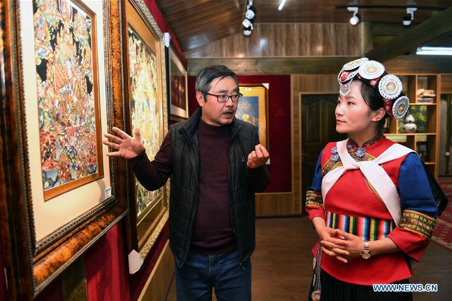Fan Yongzhen (R), deputy to China\'s 13th National People\'s Congress (NPC), carries out a research on Thangka Budda Painting with dianxiu embroidery at Baisha Old Town of Yulong Naxi Autonomous County in Lijiang, southwest China\'s Yunnan Province, Feb. 13, 2019. Working as vice curator of the Cultural Center in Lijiang city, Fan has devoted herself to the career of protecting and promoting local ethnic cultures. Besides, she also contributes to the mass culture construction work by sending performances to rural areas together with her colleagues. As a deputy to NPC, China\'s top legislature, Fan will put more efforts into the building of cultural industries integrated with digital technologies in underdeveloped areas so as to improve local cultural development. (Xinhua/Yang Zongyou)
