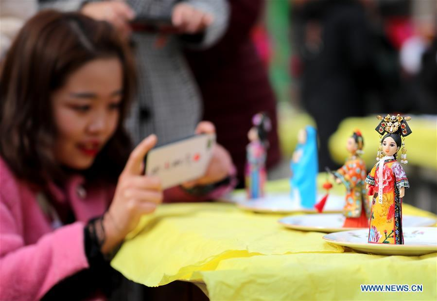 A visitor takes a photo of the dough modelling on the annual dough modelling exhibition held in Nanzhang Village of Xiulin Town in Jingxing County, Shijiazhuang, capital of north China\'s Hebei Province, on Feb. 22, 2019. The exquisitely crafted and colorful dough modelling on display attracted a great number of visitors to appreciate the beauty. The Nanzhang dough modelling was listed as one of the provincial level intangible cultural heritages in 2011. (Xinhua/Wang Baolong)