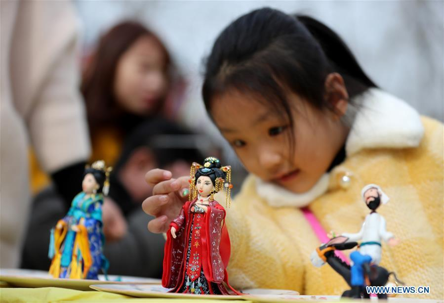 A child watches the dough modelling exhibited on the annual dough modelling exhibition held in Nanzhang Village of Xiulin Town in Jingxing County, Shijiazhuang, capital of north China\'s Hebei Province, on Feb. 22, 2019. The exquisitely crafted and colorful dough modelling on display attracted a great number of visitors to appreciate the beauty. The Nanzhang dough modelling was listed as one of the provincial level intangible cultural heritages in 2011. (Xinhua/Wang Baolong)