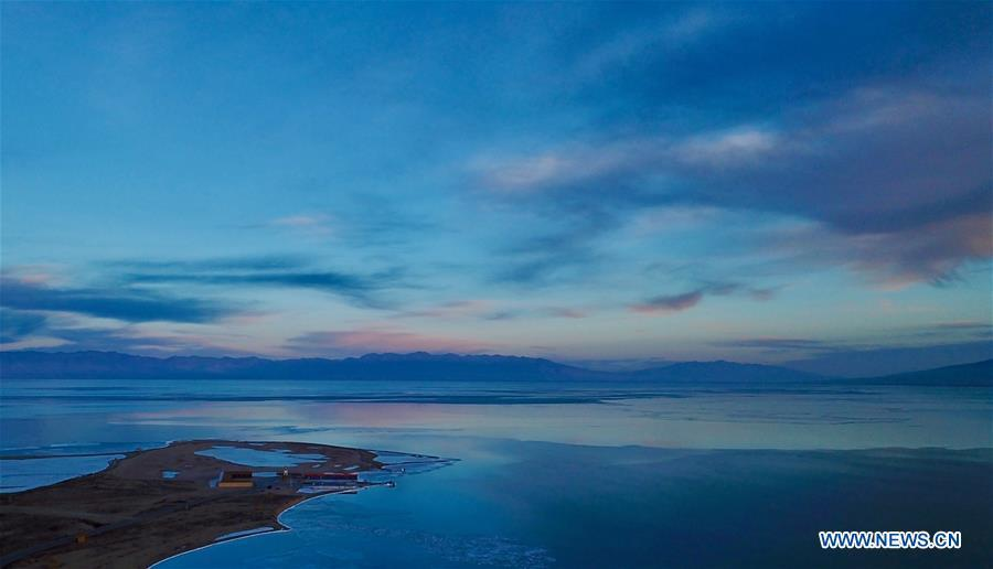Photo taken on Dec. 21, 2017 shows the sunset glow over the frozen Qinghai Lake in northwest China\'s Qinghai Province. China\'s largest inland saltwater lake saw its water level rise 0.48 meters in 2018 as a result of increased rainfall, the local meteorological center said. Qinghai Lake, situated in northwest China\'s Qinghai Province, has been expanding since 2005. The water level rose to 3,195.41 meters at the end of last year, according to the Qinghai hydrology and water resources investigation bureau. Experts said the rising level of the lake could help increase the area\'s humidity and temperature, which contributes to the improvement of the region\'s wildlife habitat and ecosystem. (Xinhua/Jia Haiyuan)