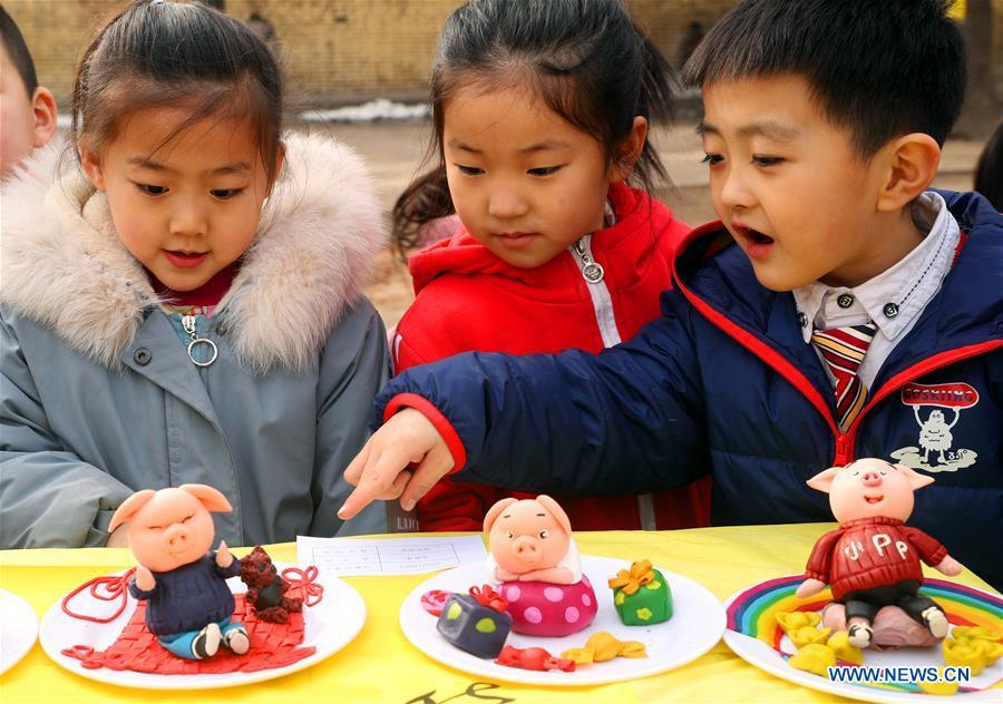 Three children watch the dough modelling on the annual dough modelling exhibition held in Nanzhang Village of Xiulin Town in Jingxing County, Shijiazhuang, capital of north China\'s Hebei Province, on Feb. 22, 2019. The exquisitely crafted and colorful dough modelling on display attracted a great number of visitors to appreciate the beauty. The Nanzhang dough modelling was listed as one of the provincial level intangible cultural heritages in 2011. (Xinhua/Zhang Xiuke)