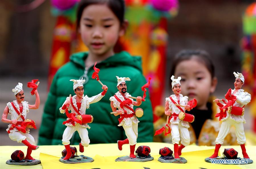 Two children watch the dough modelling exhibited on the annual dough modelling exhibition held in Nanzhang Village of Xiulin Town in Jingxing County, Shijiazhuang, capital of north China\'s Hebei Province, on Feb. 22, 2019. The exquisitely crafted and colorful dough modelling on display attracted a great number of visitors to appreciate the beauty. The Nanzhang dough modelling was listed as one of the provincial level intangible cultural heritages in 2011. (Xinhua/Wang Baolong)