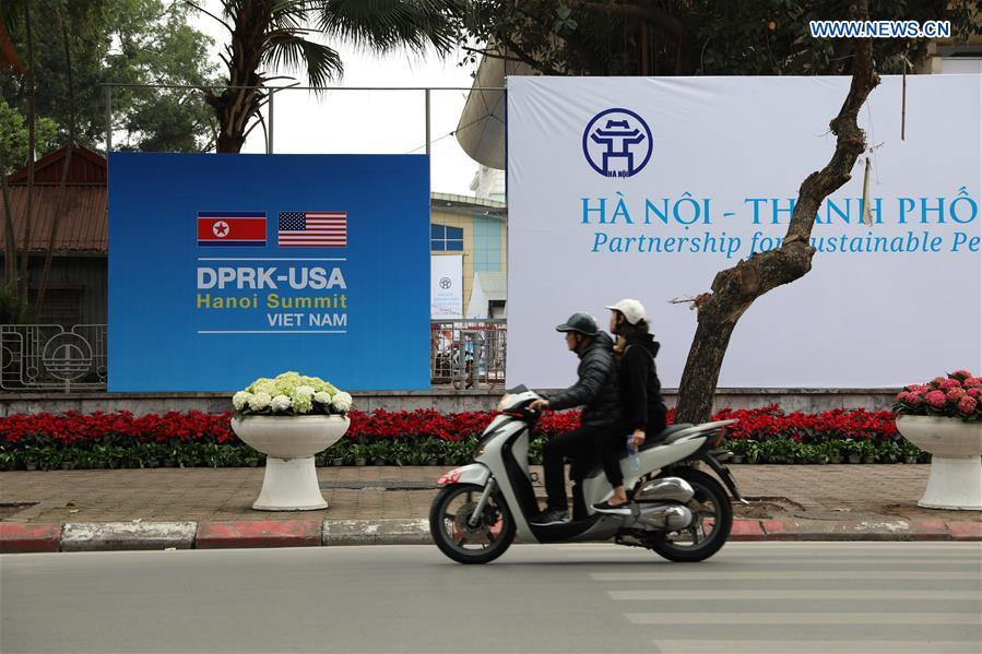 People pass by the International Media Center for the second summit between the Democratic People\'s Republic of Korea (DPRK) and the United States in Hanoi, Vietnam, on Feb. 24, 2019. The second DPRK-U.S. summit is scheduled to be held in Hanoi on Feb. 27-28. (Xinhua/Wang Di)