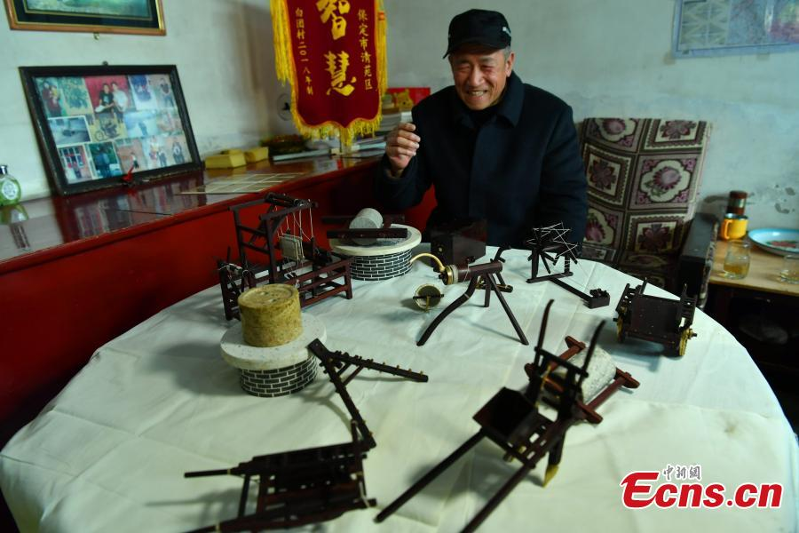 Wang Xiangcheng shows his handmade miniature agricultural tools in his home in a village in Baoding City, North China\'s Hebei Province, Feb. 25, 2019. Wang has built more than a dozen sets of models of old farming objects, such as ploughs, carriages, looms and stone mills, at a scale of 1:8. He said he hoped his models could provide younger generations with a glimpse of what life was like in the countryside in years past. (Photo: China News Service/Zhai Yujia)