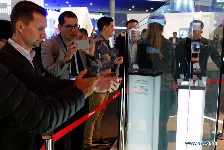 Visitors take pictures of a Huawei MATE X, a foldable 5G ready smartphone, displayed at the 2019 Mobile World Congress (MWC) in Barcelona, Spain, Feb. 25, 2019. The four-day 2019 MWC opened on Monday in Barcelona. (Xinhua/Guo Qiuda)