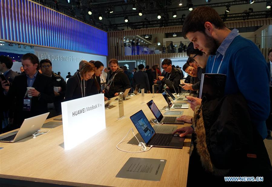 Visitors try on Huawei MateBook X Pro laptops at the 2019 Mobile World Congress (MWC) in Barcelona, Spain, Feb. 25, 2019. The four-day 2019 MWC opened on Monday in Barcelona. (Xinhua/Guo Qiuda)