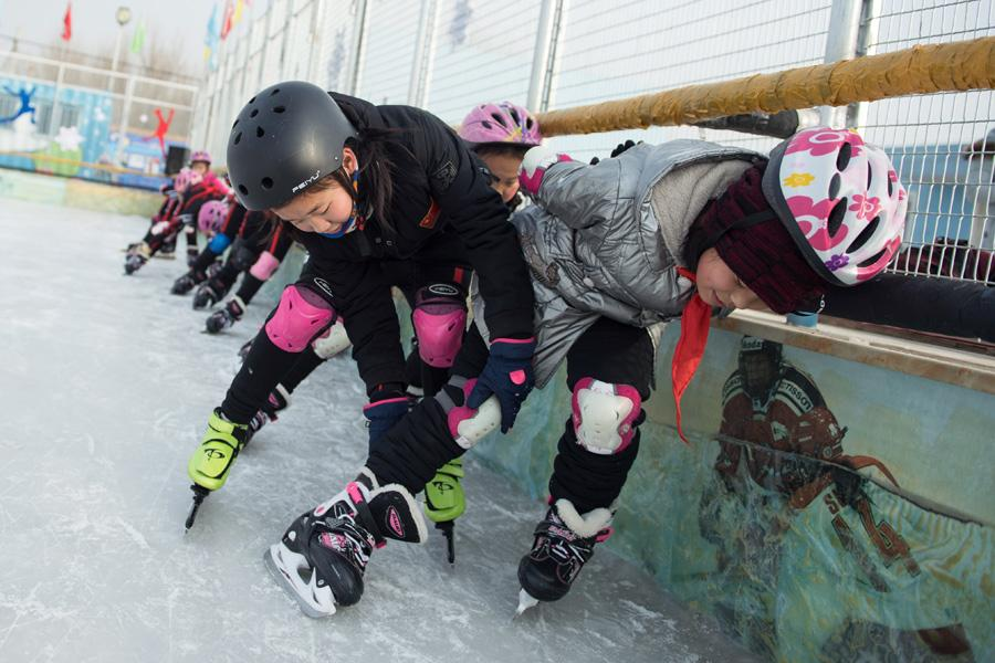 Students at Beijing Yanqing Taipingzhuang Central Primary School practice skating on the ice rink. (Photo/Xinhua) \
