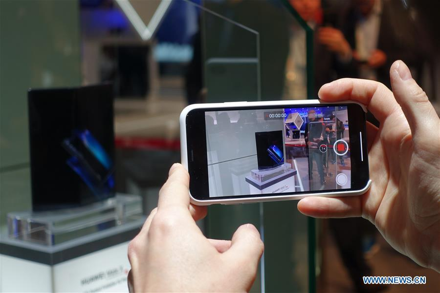 A visitor takes pictures of a Huawei MATE X, a foldable 5G ready smartphone, displayed at the 2019 Mobile World Congress (MWC) in Barcelona, Spain, Feb. 25, 2019. The four-day 2019 MWC opened on Monday in Barcelona. (Xinhua/Guo Qiuda)
