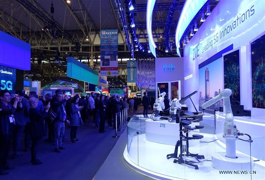 Visitors take pictures of a ZTE drum robot at the 2019 Mobile World Congress (MWC) in Barcelona, Spain, Feb. 25, 2019. The four-day 2019 MWC opened on Monday in Barcelona. (Xinhua/Guo Qiuda)