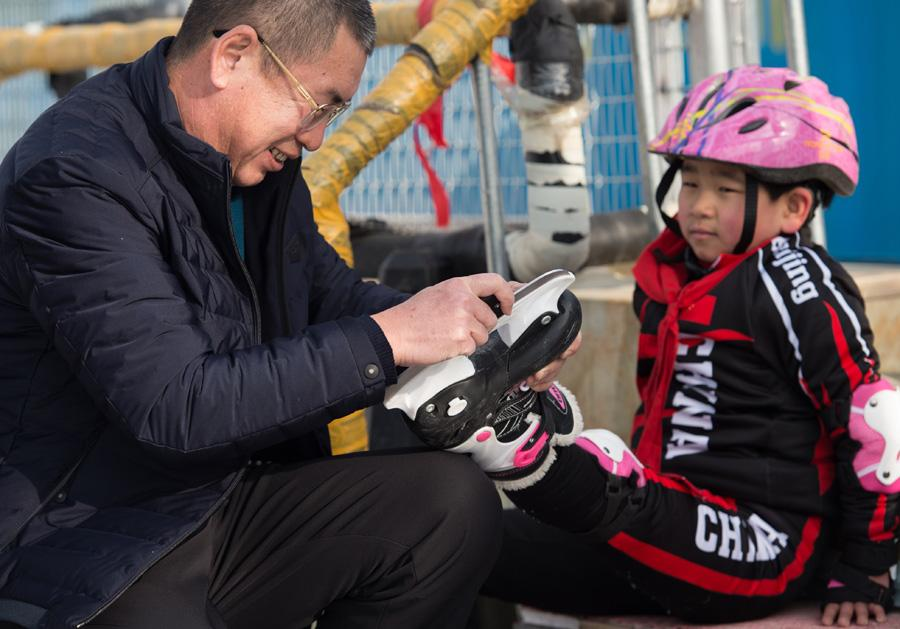 Ding Jianpei, the headmaster of the school (left in the above picture), hopes the students can really enjoy winter sports while growing up.  (Photo/Xinhua)