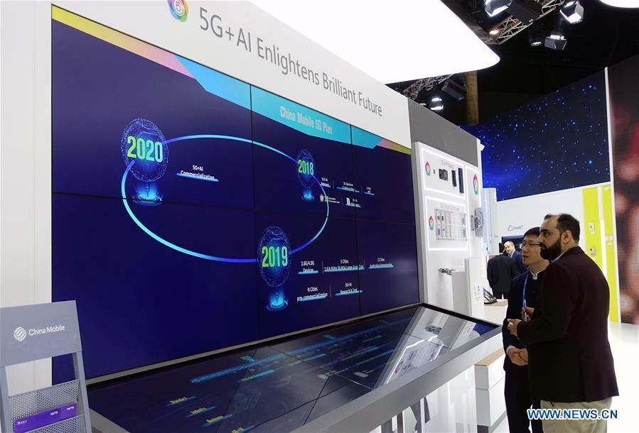 A visitor learns China Mobile 5G plan at Mobile World Congress (MWC 2019) in Barcelona, Spain, Feb. 26, 2019. The four-day MWC 2019 opened its door on Monday, which presents the newest 5G products of the high-tech giants from all around the world. (Xinhua/Guo Qiuda)