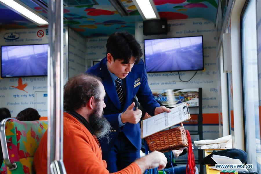 Lee Tae-hyun (R), a trainman and tour guide, registers a passenger\'s information onboard a DMZ train, South Korea, Feb. 20, 2019. Created in 1953 when the three-year Korean War ended with armistice, the Demilitarized Zone (DMZ) has long been a symbol of both confrontation and peace as tensions or rapprochement across the inter-Korean border can be felt firsthand in the 250-km-long strip of no-man\'s land. The DMZ Train departed Seoul Station for Dorasan Station, the northernmost station of the ROK just about 50 km north of Seoul and only 700 meters south of the southern boundary of the 4-km-wide DMZ. (Xinhua/Wang Jingqiang)