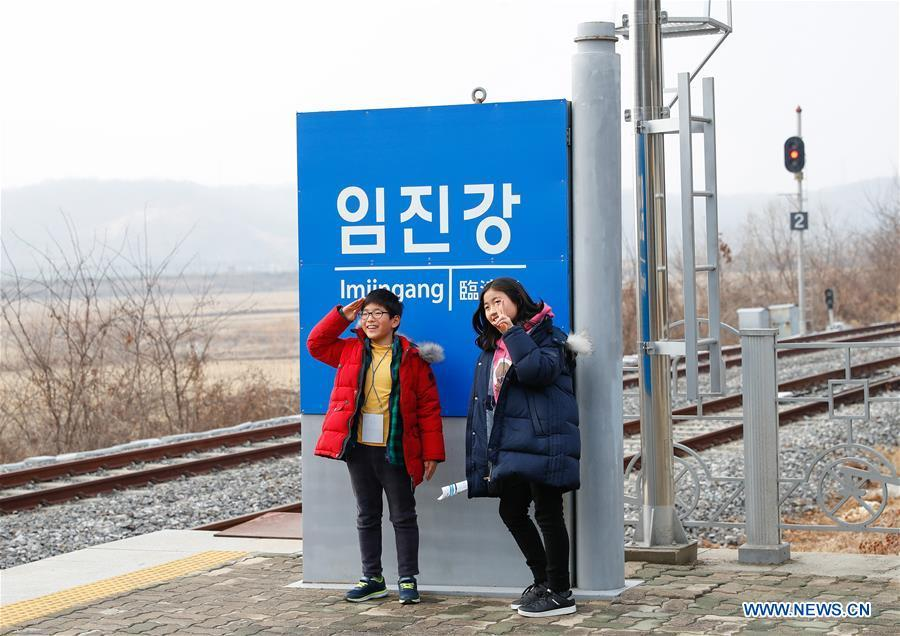 Two children pose for photos at the Imjingang Station in Paju, South Korea, Feb. 20, 2019. Created in 1953 when the three-year Korean War ended with armistice, the Demilitarized Zone (DMZ) has long been a symbol of both confrontation and peace as tensions or rapprochement across the inter-Korean border can be felt firsthand in the 250-km-long strip of no-man\'s land. The DMZ Train departed Seoul Station for Dorasan Station, the northernmost station of the ROK just about 50 km north of Seoul and only 700 meters south of the southern boundary of the 4-km-wide DMZ. (Xinhua/Wang Jingqiang)