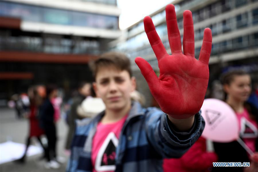 A boy shows his hand covered with red color that represents attitude towards peer violence during the Pink Shirt Day event calling for the prevention of peer violence, in Sarajevo, Bosnia and Herzegovina (BiH), on Feb. 27, 2019. The event held in the city center of Sarajevo on Wednesday attracted several hundred residents, who were informed about how to recognize the peer violence, and how to prevent it through conversation and quality time spending with a child who suffered some form of violence. (Xinhua/Nedim Grabovica)