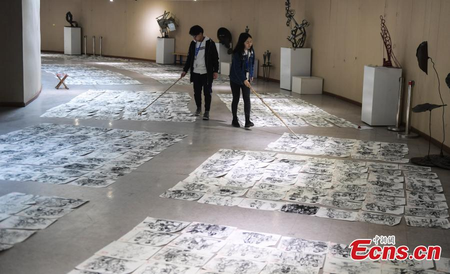 Judges use bamboo sticks to help them review paintings by applicants to the Shandong University of Arts in Jinan City, Shandong Province, Feb. 28, 2019. More than 10,000 paintings were placed in a corridor for judges to grade. (Photo: China News Service/Zhang Yong)
